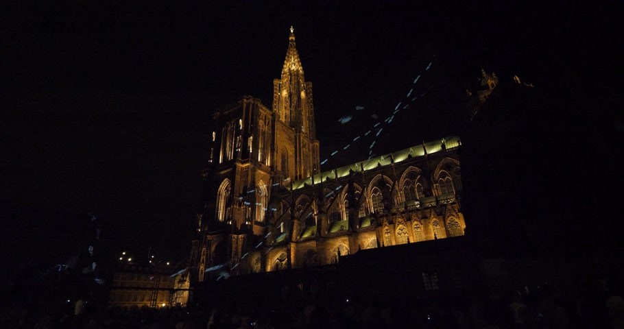 strasbourg : STRASBOURG, FRANCE - AUG 2018: Laser light show with Notre-Dame de Strasbourg cathedral in the background steps  during summer night with holographic image projected on thin mesh Stock Footage