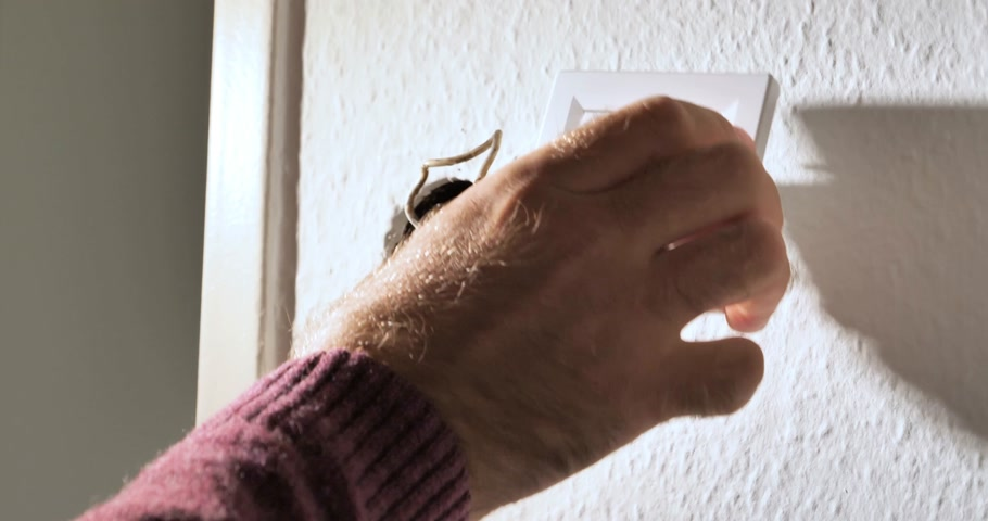 fitter : PARIS, FRANCE - CIRCA 2018: Time-lapse fast motion professional man repairing household power, dismantling faulty wall switch light, changing a light switch with a new one from Schneider Electric - side light illumination