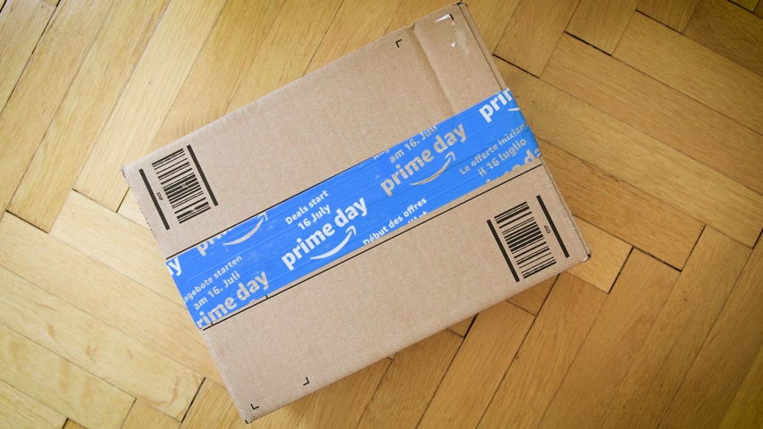amazon prime : PARIS, FRANCE - JUL 12: Rotation over Amazon Prime Day cardboard parcel on wooden parquet floor with special blue scotch tape for the Prime Day offering a day of deals, discounts, and great shopping Stock Footage