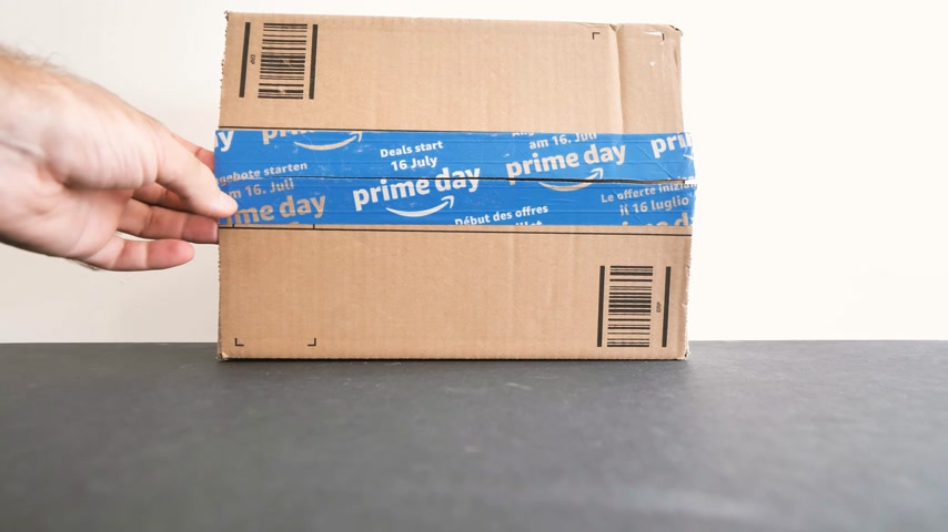amazon prime : PARIS, FRANCE - JUL 12: Curious man unboxing with cutter Amazon Prime Day cardboard parcel floor with special blue scotch tape for the Prime Day offering a day of deals, discounts, and great shopping