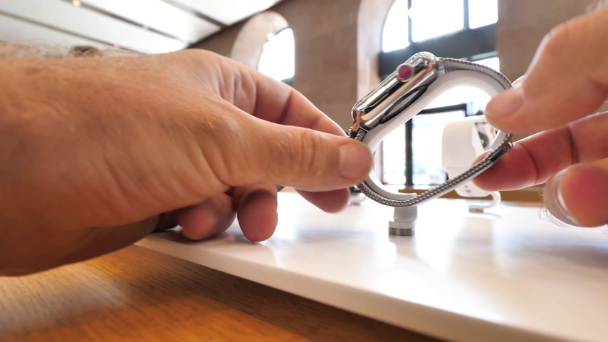 jel : PARIS, FRANCE - JUL 16, 2018: Admiring close-up steel Apple Watch series 3 in Apple Mac store main hall with touching the newest latest and most advanced wearable device deciding which one to buy