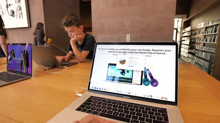 silicon : PARIS, FRANCE - JUL 16, 2018: Apple Store scene with POV of man using MacOS High Sierra at latest MacBook Pro Core i9 with young boy working on the opposite side of the table on laptop