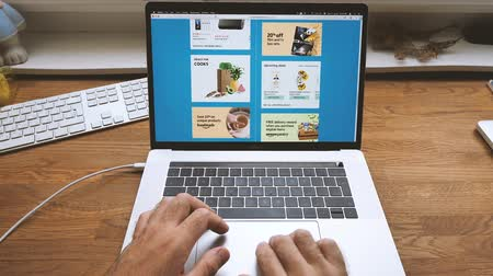 продвижение : PARIS, FRANCE - JUL 16: Man hands POV scroll shopping on Apple MacBook Pro 15 laptop with Safari Internet browser open to Shop All Deals banner on Amazon Prime Day special discounts online consumerism Стоковые видеозаписи