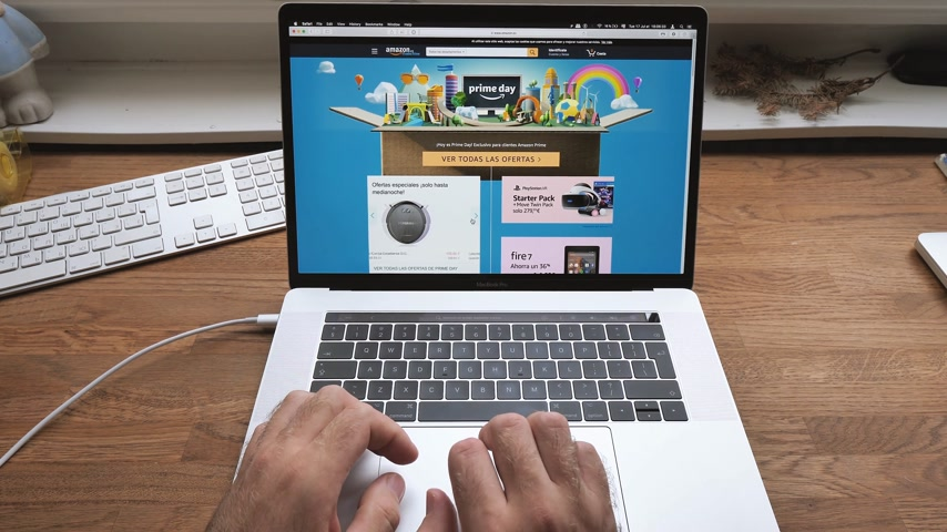 amazon prime : PARIS, FRANCE - JUL 16: Man hands POV scroll shopping on Apple MacBook Pro 15 laptop with Safari Internet browser open to Amazon Prime Day special deals discounts - consumerism shopping on French site
