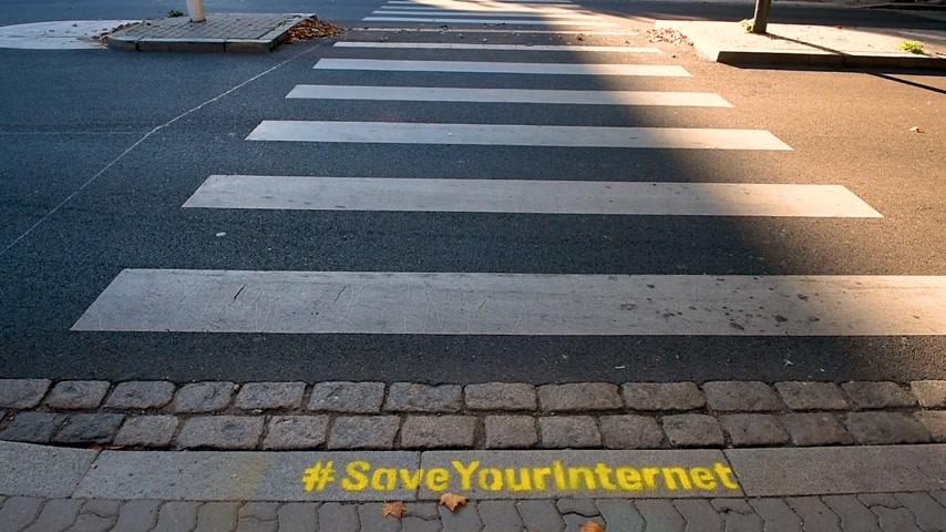 hashtag : STRASBOURG, FRANCE - SEP 12, 2018: Saveyourinternet protest sign as EU votes to adopt controversial copyright law that could ban memes and destroy the internet - Strasbourg street crossing with cars