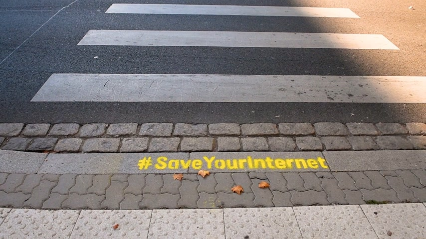 neutrality : STRASBOURG, FRANCE - SEP 12, 2018: Saveyourinternet protest sign as EU votes to adopt controversial copyright law that could ban memes and destroy the internet - Strasbourg street with cars
