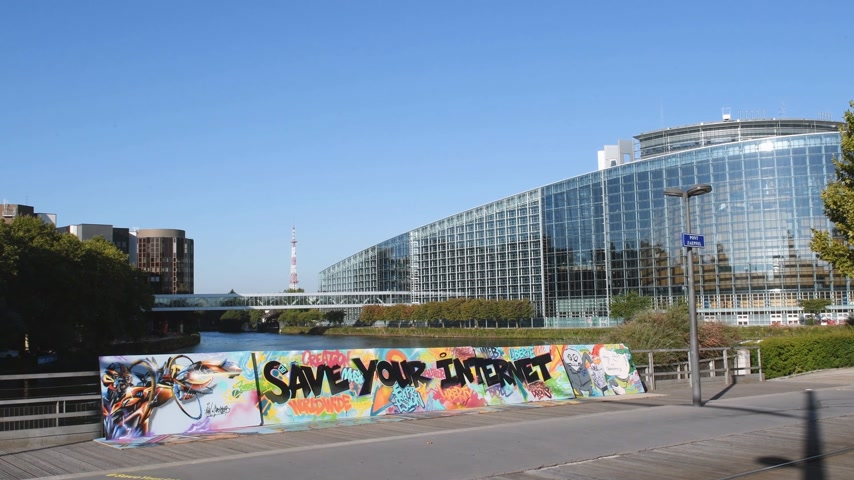 hashtag : STRASBOURG, FRANCE - SEP 12, 2018: Wide image of  large protest banner Save Your Internet with European parliament in the background couple walking in the background