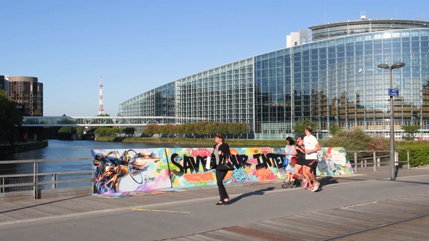 neutrality : STRASBOURG, FRANCE - SEP 12, 2018: Pedestrians families runners in front of wide image of  large protest banner Save Your Internet with European parliament in the background