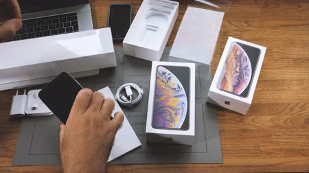 film plastique : Paris, France - 21 septembre 2018: Apple fan boy unboxing dernier modèle de téléphone mobile smartphone phare Apple iPhone Xs Max et Xs de Apple Computers enlever film plastique