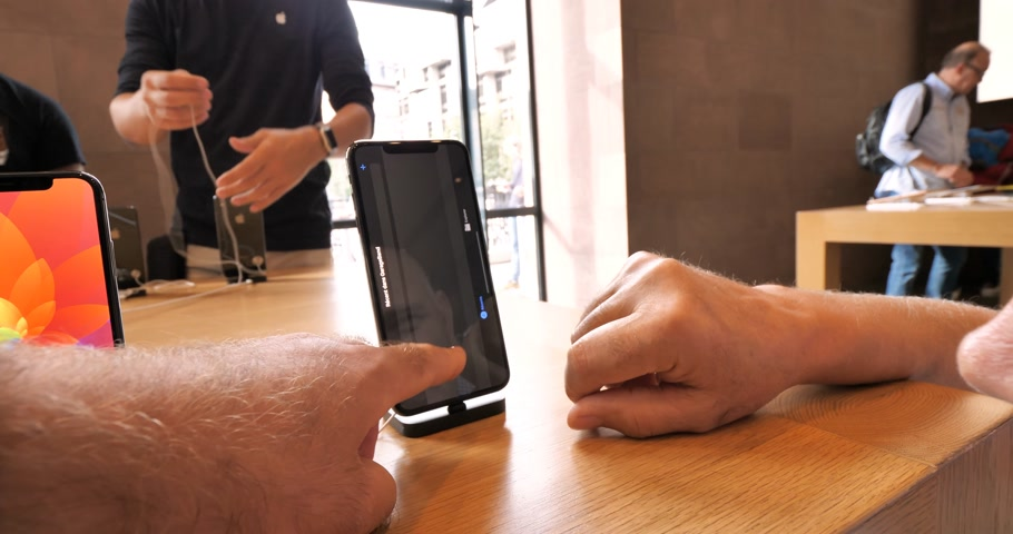 app store : STRASBOURG, FRANCE - SEP 21, 2018: Senior man using GarageBand music creation app on the new iPhone Xs Max in Apple Store during Launch day of new smartphones time-lapse fast motion Stock Footage