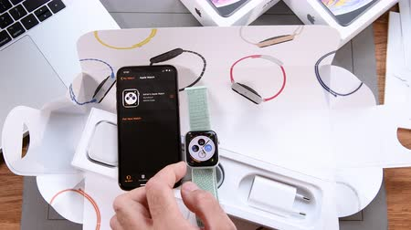 ecg : PARIS, FRANCE - SEPTEMBER 21, 2018: Apple fan boy unboxing latest new Apple Watch Series 4 GPS LTE Silver Aluminum Case with Seashell Sport Loop wearable smartwatch from Apple Computers first run logo on screen - diverse clock face setting
