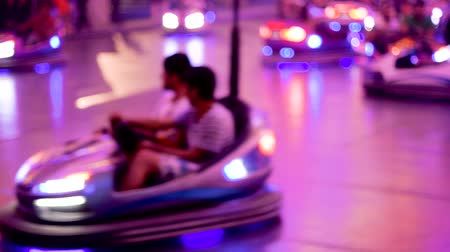 luna : Defocused view of bumper car attraction nighttime view of funny atmosphere at the amusement park 4K UHD cinematic camera used - funny Friday night Stock Footage