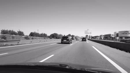 митрополит : STRASBOURG HOENHEIM, FRANCE - CIRCA 2018: Driver POV at cars driving on Autoroute de lEst leaving Strasbourg toward Paris - driving near the car dealers buildings, industrial equipment renting etc - 4k UHD footage black and white