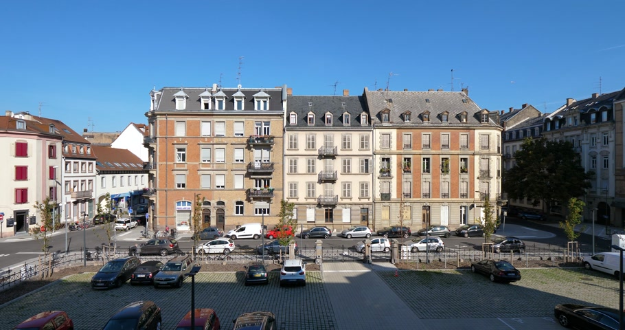 paris : STRASBOURG, FRANCE - CIRCA 2018: Saturday morning over the beautiful apartments building in French city of Strasbourg on the Rue Graumann - elevated view real estate in France, cars, pedestrians blue sky - cathedrals bells in the background sound Stock Footage
