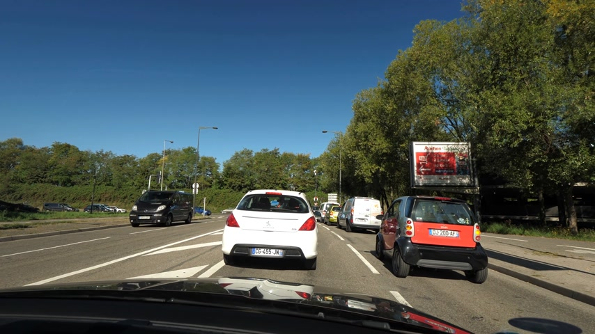 reçel : STRASBOURG HOENHEIM, FRANCE - CIRCA 2018: Driver POV at cars in traffic jam before entering the A350 national highway national route from Avenue Herrenschmidt road on a newly asphalted road in France - Driver POV sunny clear sky Stok Video
