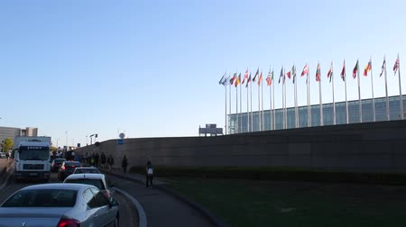 strasbourg : STRASBOURG, FRANCE - CIRCA 2018: Cars traffic jam in front of European Parliament building during the Parliamentary Assemblee days with security soldiers inspecting people workers and cars - flags waving background