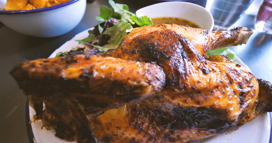 oven chicken : Zoom out from delicious prepared chicken in oven with traditionally baked potatoes on French restaurant table - yummy fat food