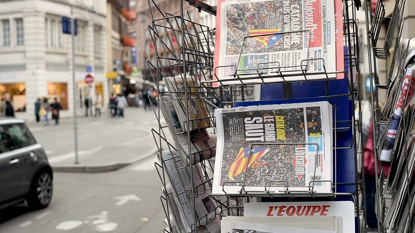 buy newspaper : PARIS, FRANCE - CIRCA 2017: French newspapers covers with Spanish referendum result after the final vote for the independence of Catalonia - French city in background with people pedestrians buildings