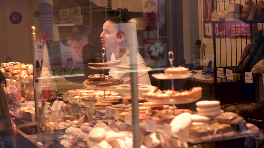 giveaway : PARIS, FRANCE - CIRCA 2018: Senior woman buying delicious sweets pastries in French patisserie cafe - view from the street of with pedestrians walking reflected in the showcase glass Stock Footage