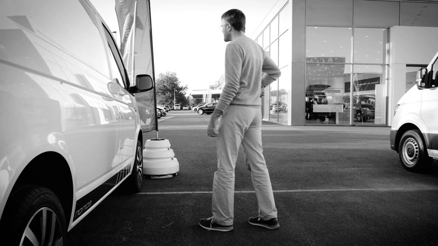 volkswagen : LYON, FRANCE - CIRCA 2018: Curious Caucasian young customer taking decision to buy new Volkswagen transporter van produced sold by Volkswagen Commercial Vehicles in front of showroom - black and white