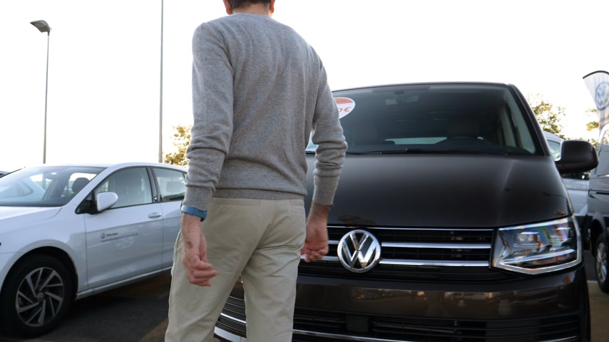 volkswagen : LYON, FRANCE - CIRCA 2018: Curious Caucasian young customer admiring the brown Volkswagen Vw transporter van offered by Vw Das Welt car dealer - checking the price and discounts of 1500 euros Stock Footage
