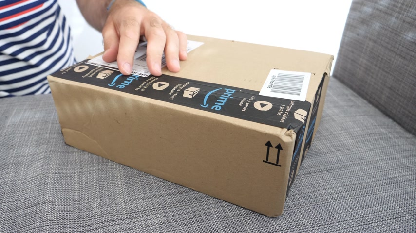 záložka : MUNICH, GERMANY - CIRCA 2018: Man unboxing on the sofa the newly arrived package parcel from Amazon Prime - curiosity opening the box with cutter Dostupné videozáznamy