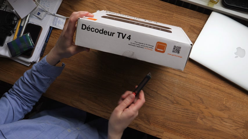 sintonizador : PARIS, FRANCE - CIRCA 2018: View from above of French woman unboxing new Orange Telecom Decoder 4 used for fiber optic and adsl tv reception open the box with cutter
