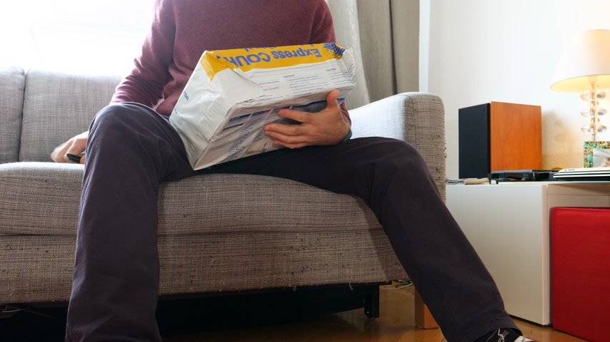 post room : PARIS, FRANCE - CIRCA 2018: Man hand unboxing parcel from Australia Post EMS post parcel package received by mail