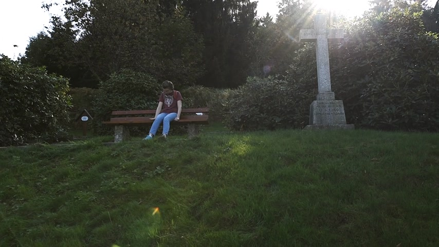 luto : Sad woman pensive sitting on the chair near the cross of a military cemetery near the Schauenburg castle ruins in Baden-Wurttemberg, Germany Stock Footage
