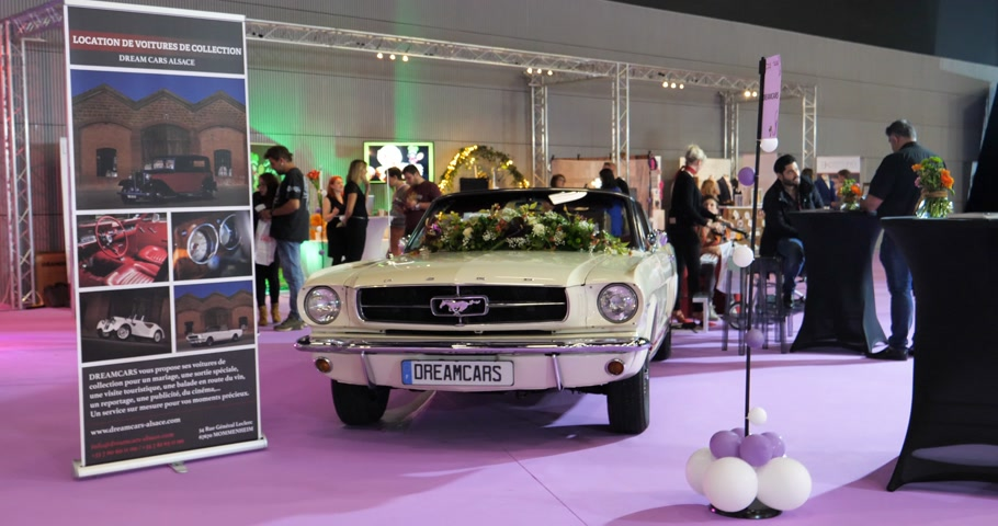 duygusallık : PARIS, FRANCE - OCT 6, 2018: Wedding Exhibition Paris 2018 with people - customers and exhibitions preparing for the marriage event vintage dream cars Mustang convertible