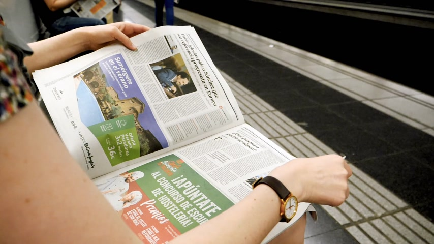 oy : BARCELONA - JUNE 1 2018: Woman reading in Barcelona Metro station the La Vanguardia newspaper slow motion footage with commuters in background on platform Spanish politics reading about