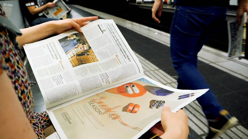 former : BARCELONA - JUNE 1 2018: Woman reading in Barcelona Metro station the La Vanguardia newspaper slow motion footage with commuters in background on platform Spanish politics reading about Pablo Iglesias