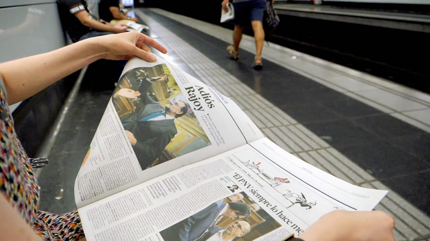 newspaper cover : BARCELONA - JUNE 1 2018: Woman reading in Barcelona Metro station the La Vanguardia newspaper slow motion footage with commuters in background on platform article Adios Rajoy