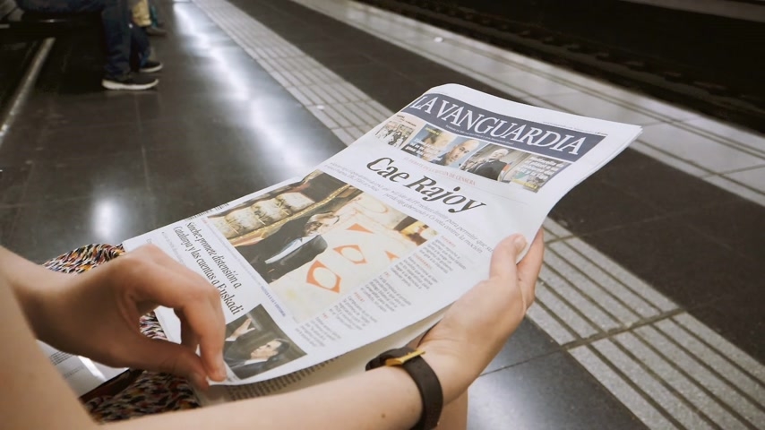 newspaper cover : BARCELONA - JUNE 1 2018: Woman reading in Barcelona Metro station the La Vanguardia newspaper cover Cae Rajoy translated as Mariano Rajoy goodbye when a vote of no confidence ousted his government slow motion- Stock Footage