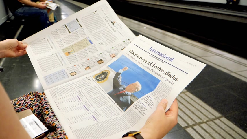 holding newspaper : BARCELONA - JUNE 1 2018: Woman reading in Barcelona Metro station the La Vanguardia newspaper slow motion footage with commuters in background on platform article about Donald Trump economics relations with China