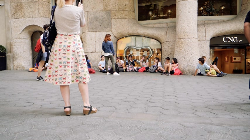 каталонский : BARCELONA, SPAIN - CIRCA 2018: Group of children eating snack at the base of La Pedrera monument on the street - slow motion footage woman taking photo on smartphone