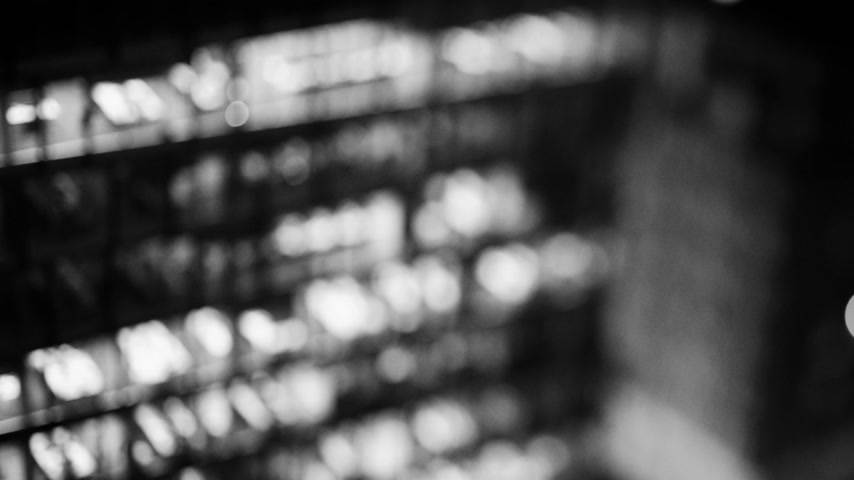 tilt shift : Aerial helicopter view to skyscraper building in banking business district in worldwide hub with working late light offices - slow focusing with a tilt-shift lens in cinematic  black and white - 4K UHD video