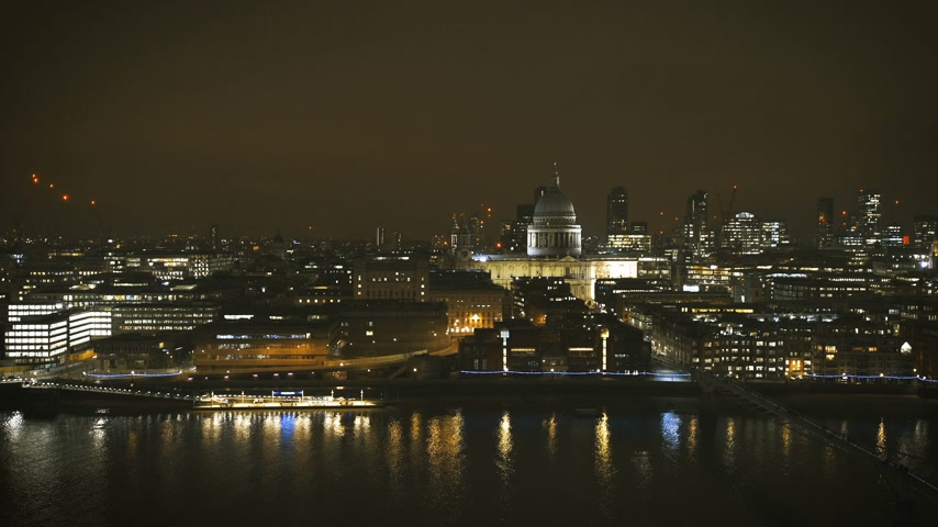 контрасты : Cinematic British London at night still drone aerial view of Anglican St Pauls Cathedral the seat of the Bishop of London and Millennium Bridge and magical Thames river skyscrapers in the background