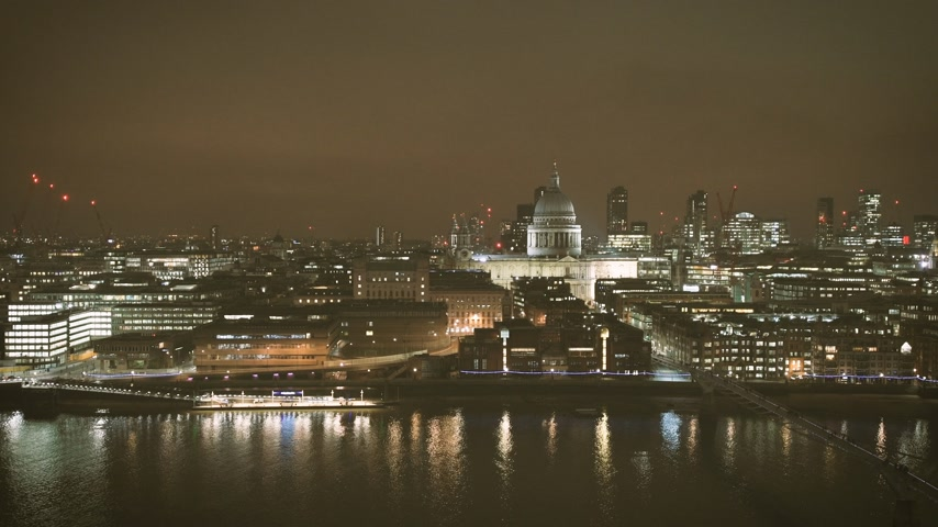 контрасты : Night scene of British London still drone aerial view of Anglican St Pauls Cathedral the seat of the Bishop of London and Millennium Bridge and magical Thames river skyscrapers in the background - cinematic news color graded