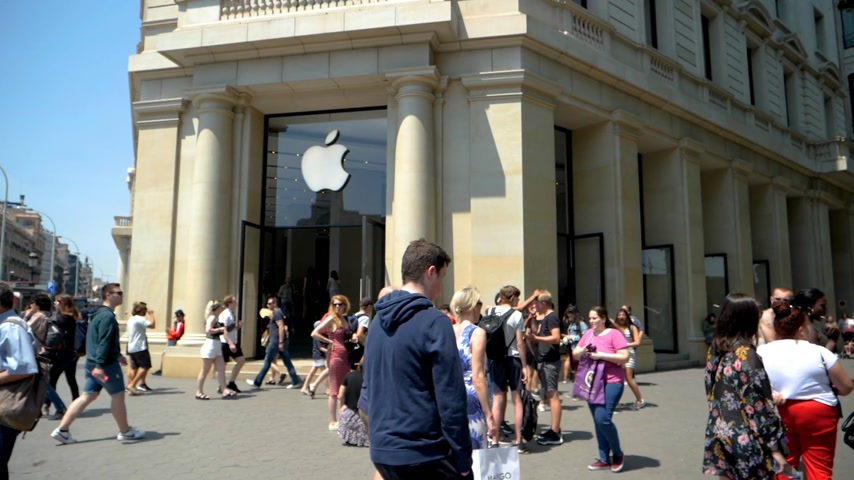производитель : BARCELONA, SPAIN - CIRCA 2018: Iconic Apple Store in central Barcelona with hundreds of people walking in slow motion on busy Passeig de Gracia on a warm summer day
