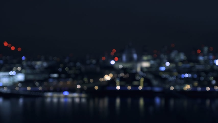 tilt shift : Defocused beautiful bokeh over cinematic British London at night still drone aerial view of Anglican St Pauls Cathedral and Millennium Bridge and magical Thames river reflection blue color cast Stock Footage