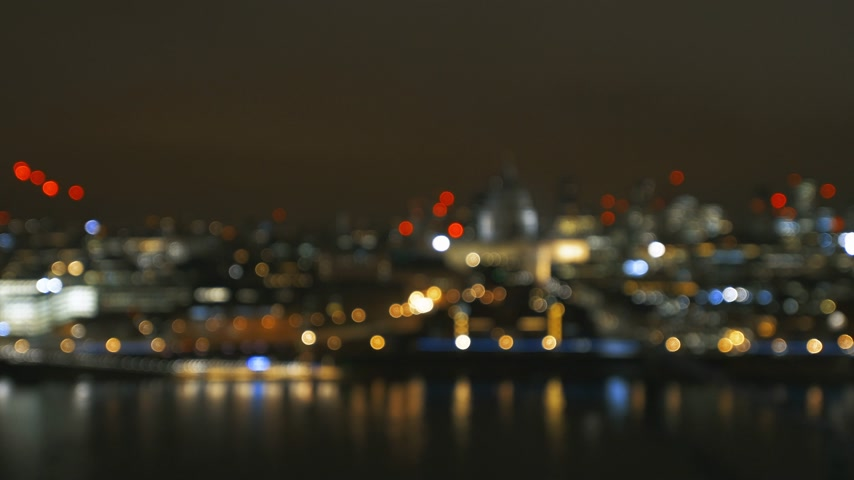 tilt shift : Defocused beautiful bokeh over cinematic British London at night still drone aerial view of Anglican St Pauls Cathedral and Millennium Bridge and magical Thames river reflection