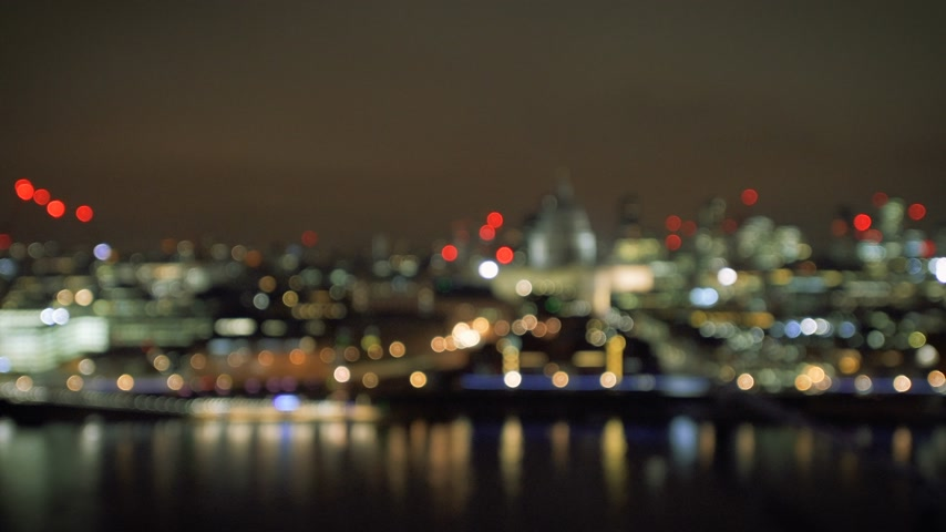 millennium : Defocused beautiful bokeh over cinematic British London at night still drone aerial view taken with real tilt-shift lens - Flickr light in background Stock Footage