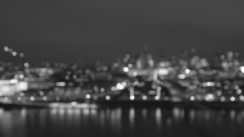 tilt : Defocused beautiful bokeh over cinematic British London at night still drone aerial view of Anglican St Pauls Cathedral and Millennium Bridge and magical Thames river reflection - black and white