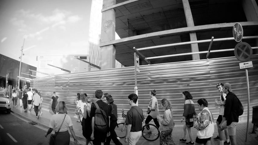turistik : BARCELONA, SPAIN - CIRCA 2018: Pedestrians walking in large groups to the Stadium of Barcelona to see football match, a concert etc. - elevated view from the street slow motion slowmotion - black and white