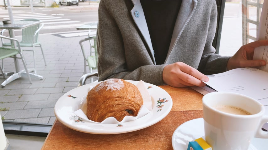 クロワッサン : Woman eating delicious croissant pain au chocolate in French cafe early in the morning drink coffee -Parisian lifestyle