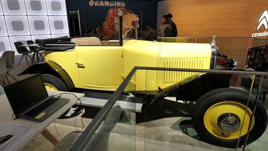 citroen : PARIS, FRANCE - OCT 4, 2018: Customers curious people admiring vintage Citroen car a exhibition Mondial Paris Motor Show - Orangina Soft Drink Bar