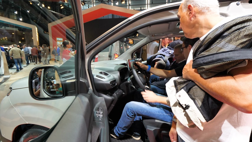 curioso : PARIS, FRANCE - OCT 4, 2018: Customers curious people admiring new French Citroen Berlingo utility van at International car exhibition Mondial Paris Motor Show