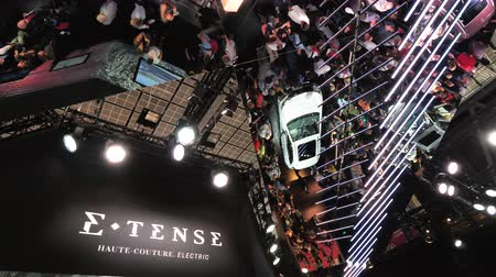 citroen : PARIS, FRANCE - OCT 4, 2018: E-Tense Haute-Couture electric logo with French Citroen DS 3 Crossback e-Tense electric car reflected on roof - exhibition stand