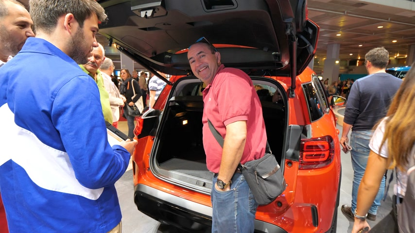 negotiate : PARIS, FRANCE - OCT 4, 2018: Customers curious people admiring new large trunk of a Citroen car at International car exhibition Mondial Paris Motor Show, Stock Footage
